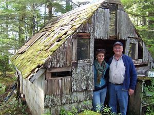 two people standing in the doorway of a wood cabin
