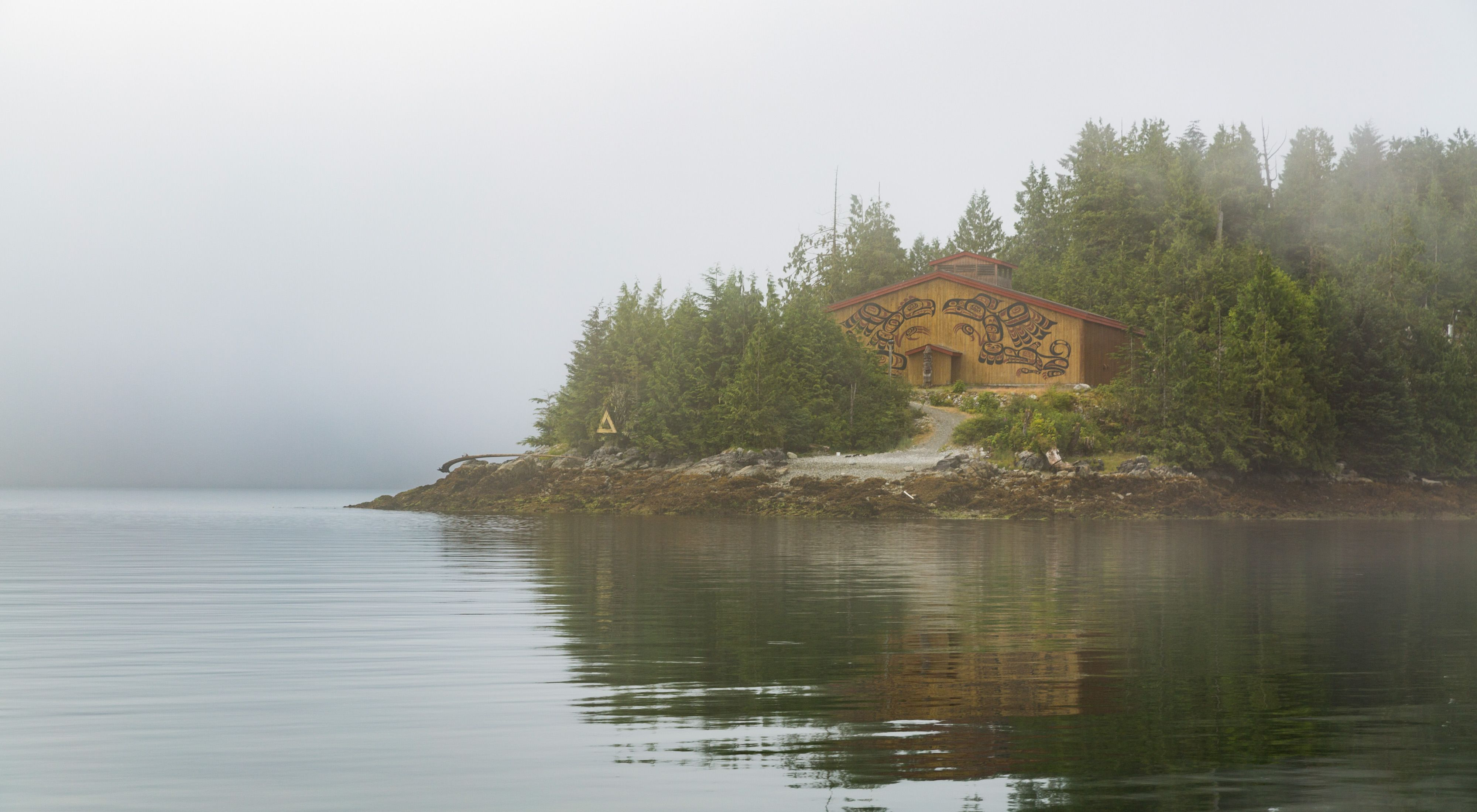 a lake reflecting a grey sky with pine trees on either side