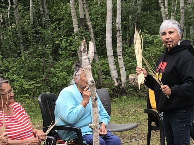 Margo双手向Misipawistik Cree Nation的成员手中分享来自Yurok部落的传统歌曲。