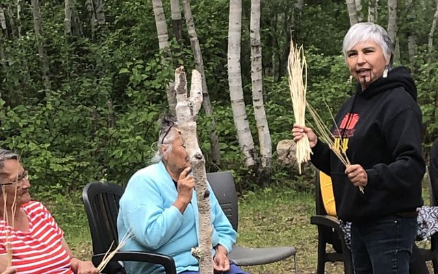 Margo hands out hazel sticks to members of the Misipawistik Cree Nation to share a traditional song from the Yurok tribe.