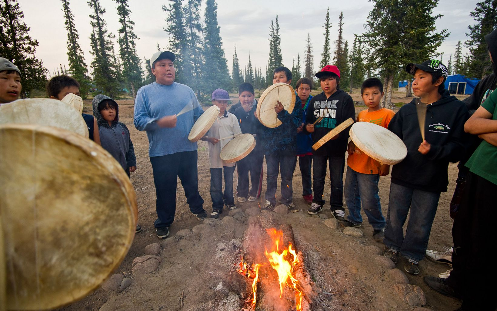 Dene First Nation youth beat drums around a fire during a spiritual gathering after returning from a canoe trip on the Upper Thelon River.