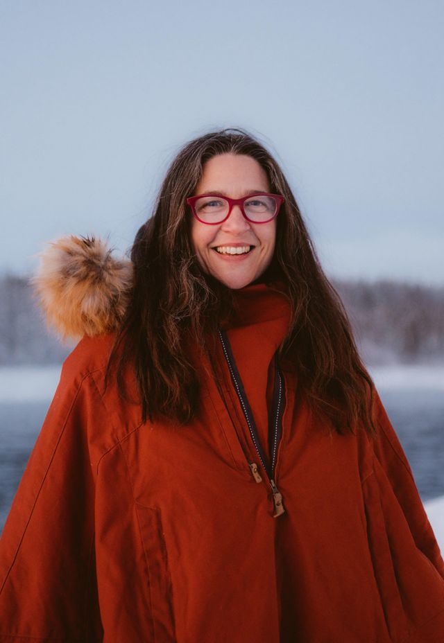 tracey williams woman stands outside near frozen lake with red parka