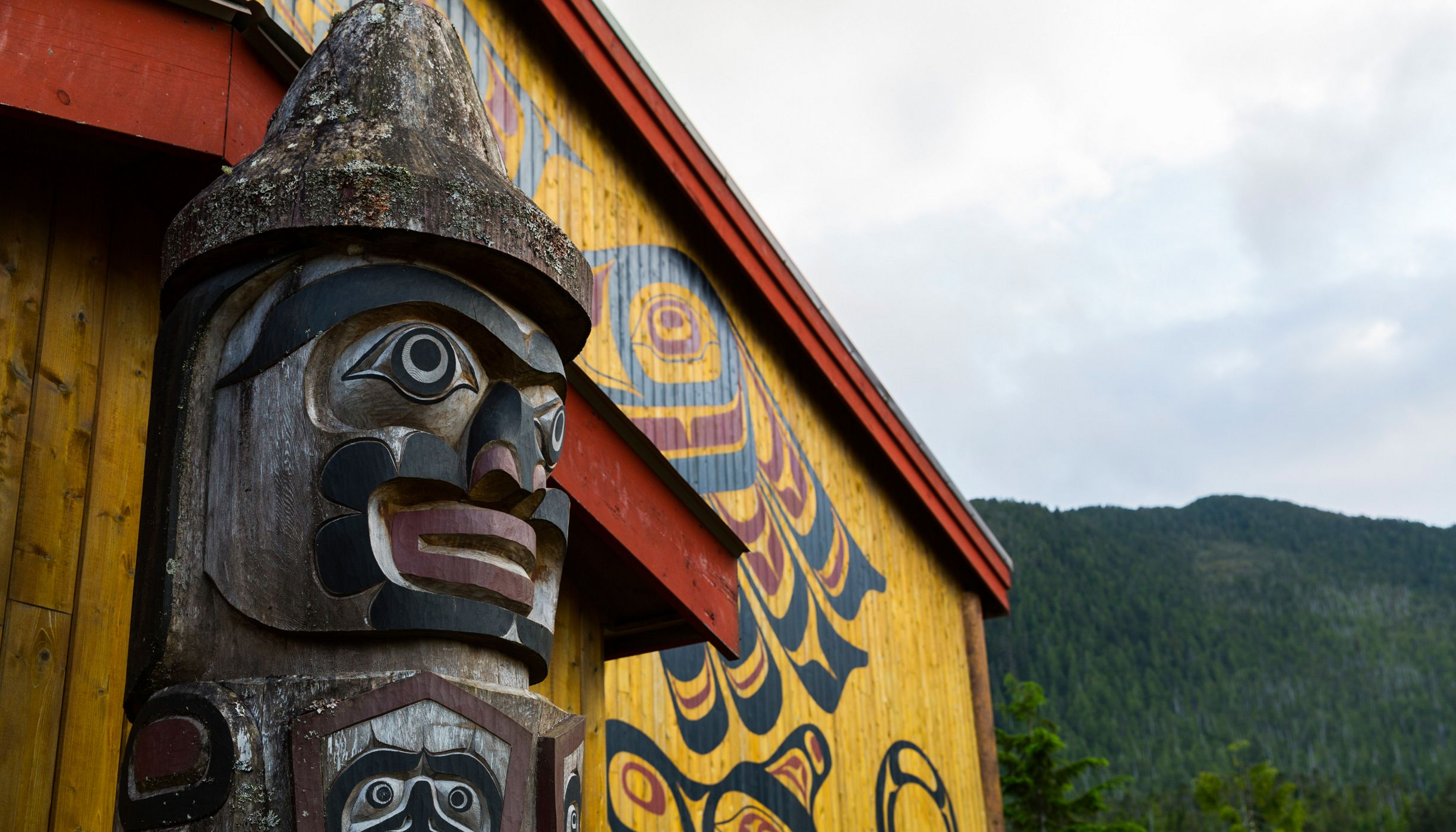 a totem pole in front of the big house in Klemtu, BC