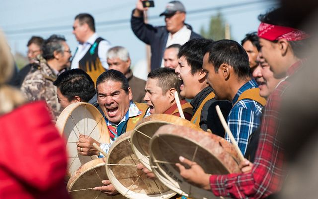 a group of men stand together and bang drums and yell