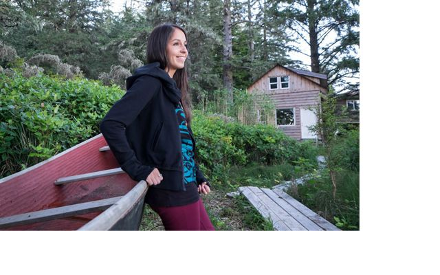 A woman leans against a wooden boat among trees in Clayoquot Sound.