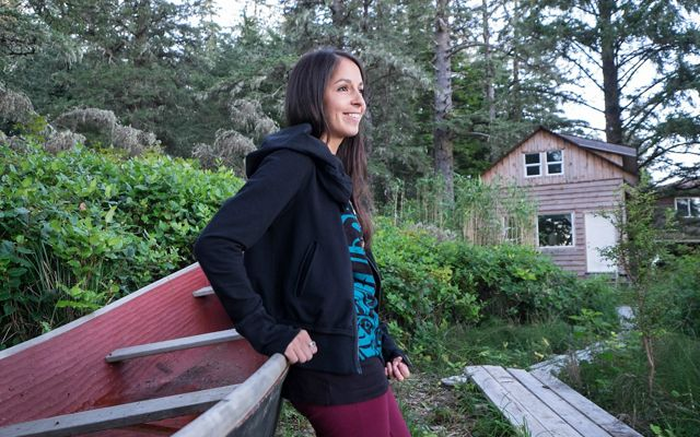一个女人斜靠在一艘木船上,在克莱奥克海峡的树林中。