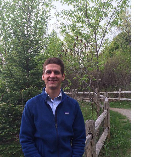 一个白人靠在一条有树的小路上的篱笆上