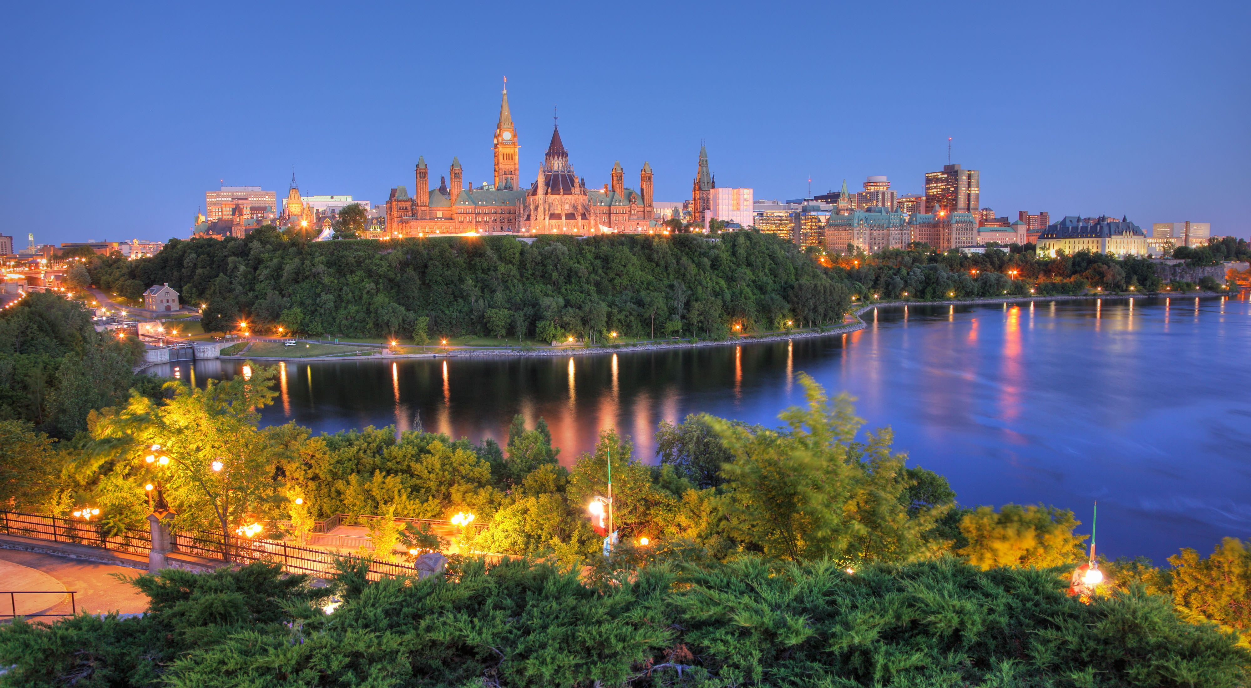 Canada's capital building lit up at night and surrounded by trees in Ottawa, Ontario.
