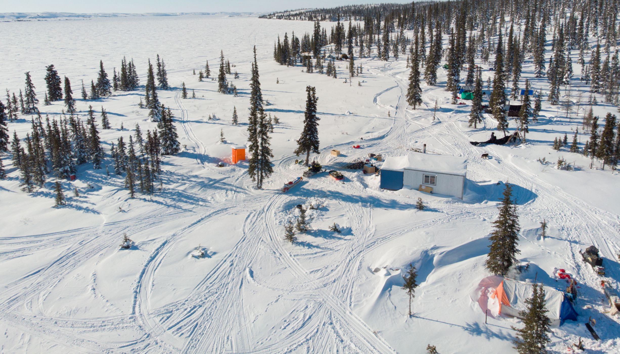 鸟瞰图的一个冰雪覆盖的景观与雪地摩托的轨道,一个小屋,几个人,和树木