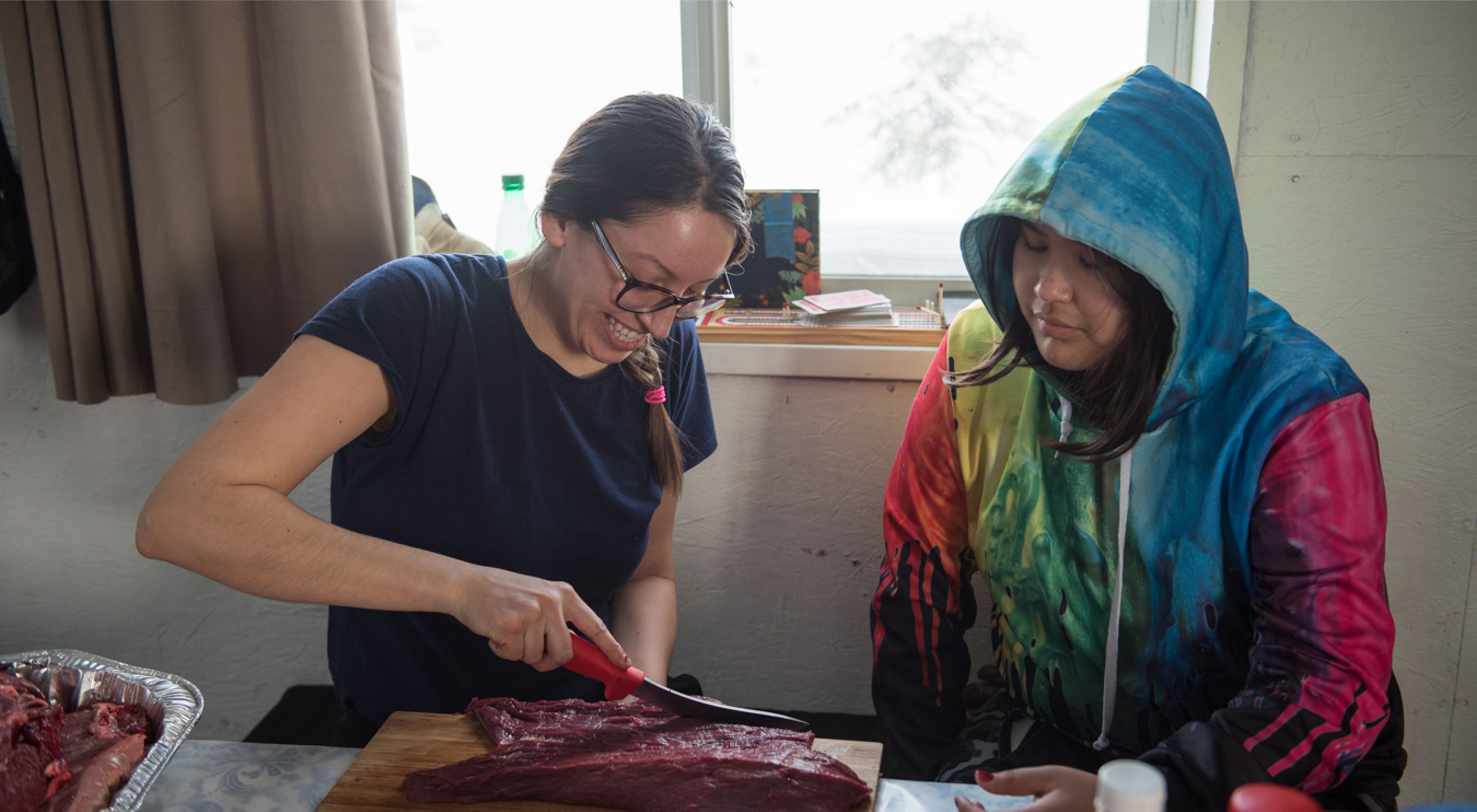 Łutsël K'é Dene First Nation member Saniz Catholique shows 12-year-old Naomi Michel how to make drymeat while at a community camp on Ɂedacho Tué (Artillery Lake).