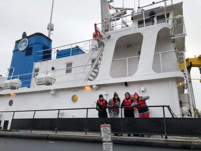 Young people from communities in the NWT, including Łutsël K'é, wave from aboard a research vessel setting sail on Tu Nedhé (also known as Great Slave Lake).