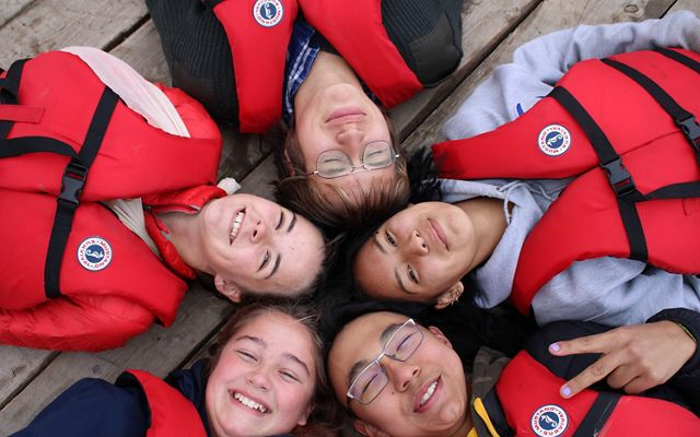 Five smiling students who sailed with Northern Youth Leadership, Arctic Foundation and Nature United on a research voyage on Great Slave Lake in 2020.