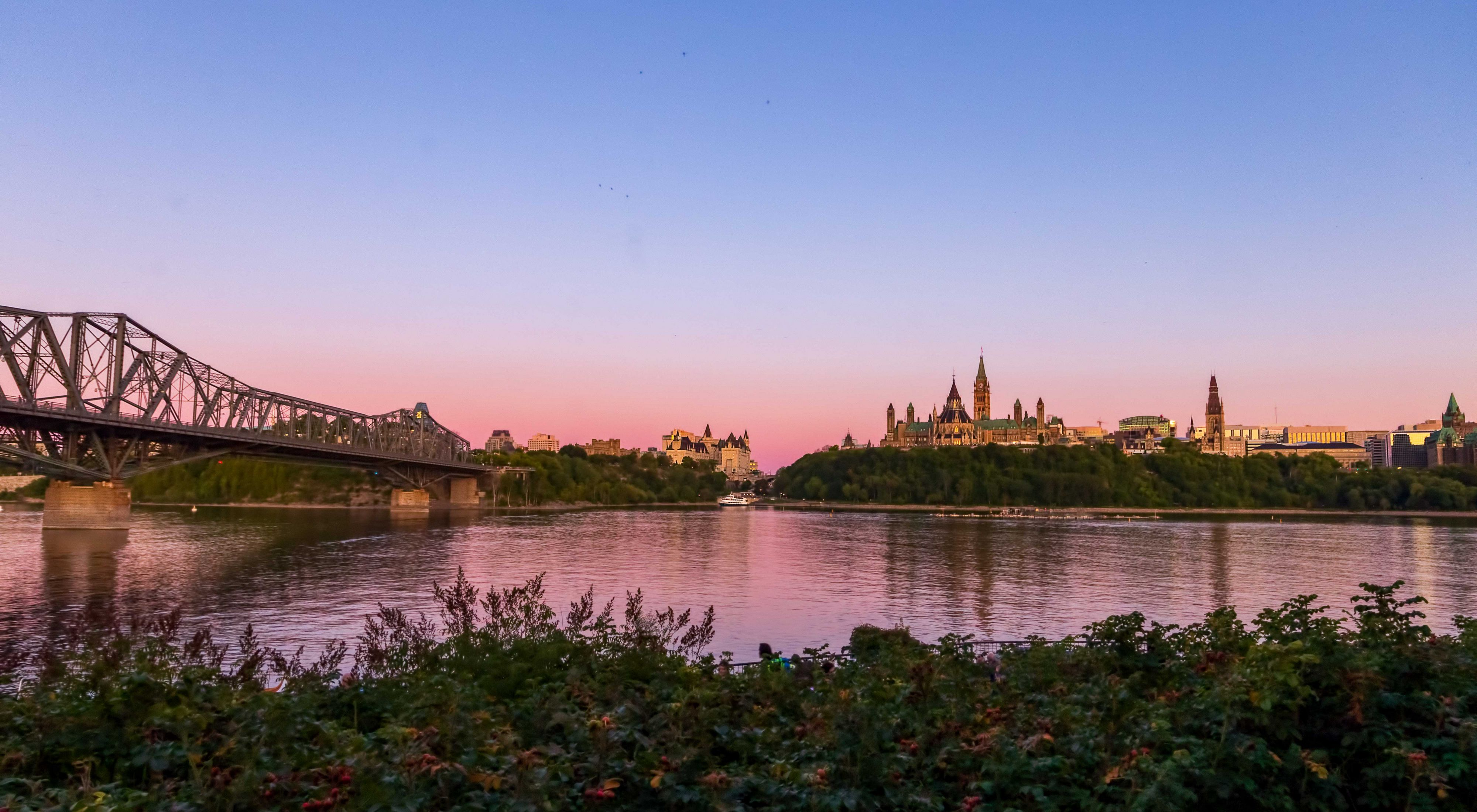 View of downtown Ottawa and the Parliament Buildings of Canada at sunset, taken from Gatineau, Quebec across the Ottawa River