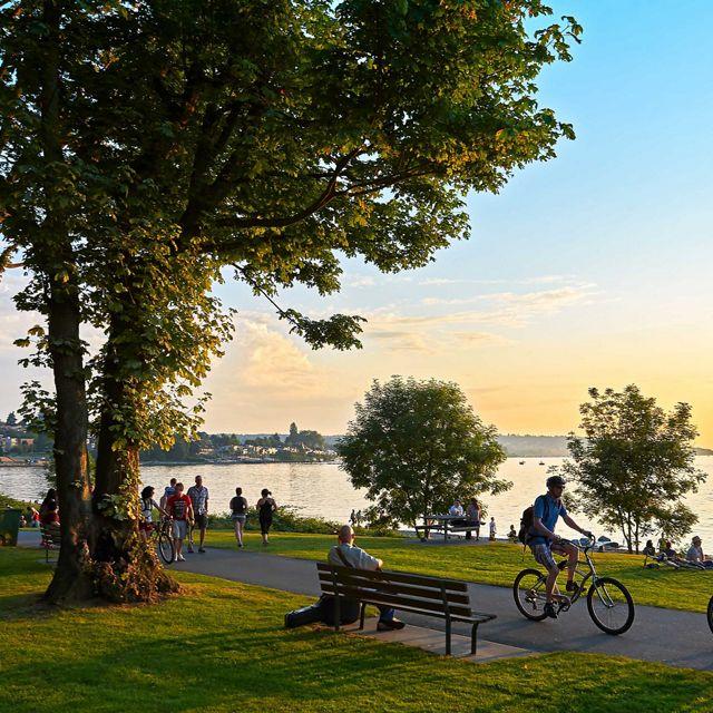 加拿大不列颠哥伦比亚省温哥华斯坦利公园,年轻夫妇骑自行车,其他人散步或慢跑,享受日落