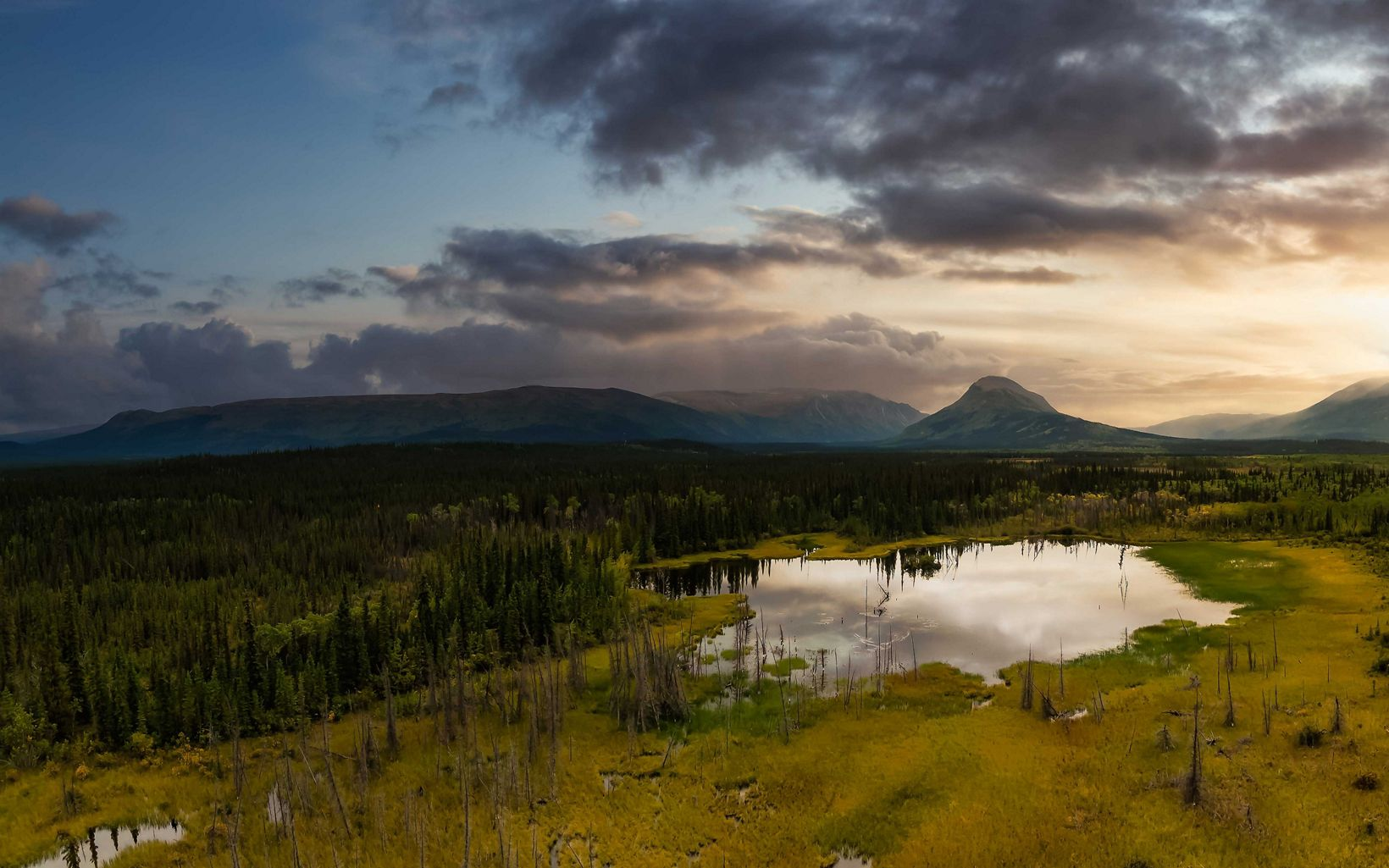 Panoramic view of pond and marshland, surrounded by forest and mountains in Yukon, Canada.