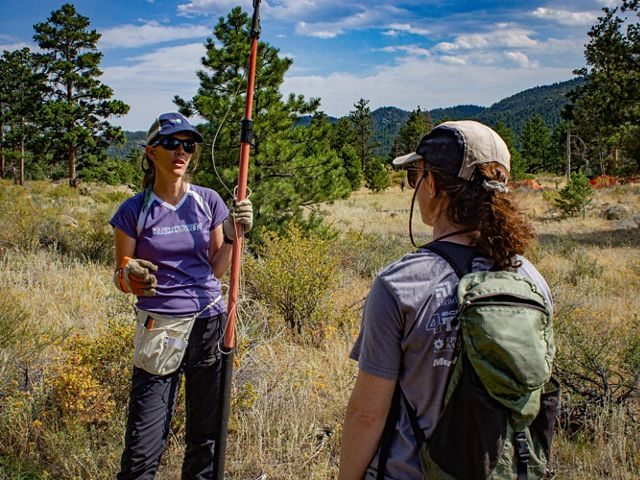 Catherine Schloegel holds a tree pruner while talking to a local researcher about seed cone collection in 2019.
