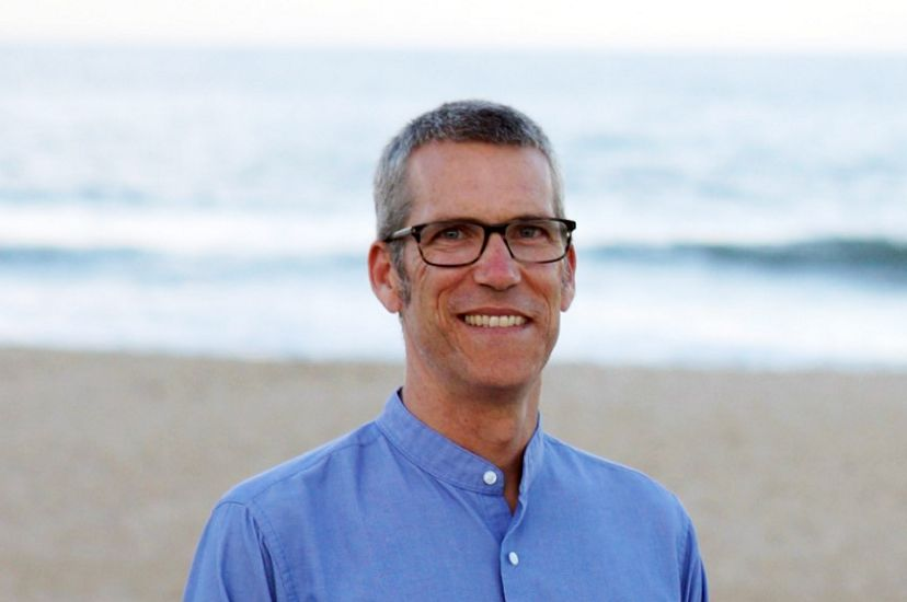 Headshot of Virginia's GIS Manager Chris Bruce. A smiling man wearing a blue shirt stands on a beach. The open water is visible behind him, stretching to the horizon.