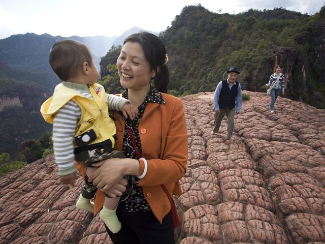 Woman smiling, holding baby walking up mountain
