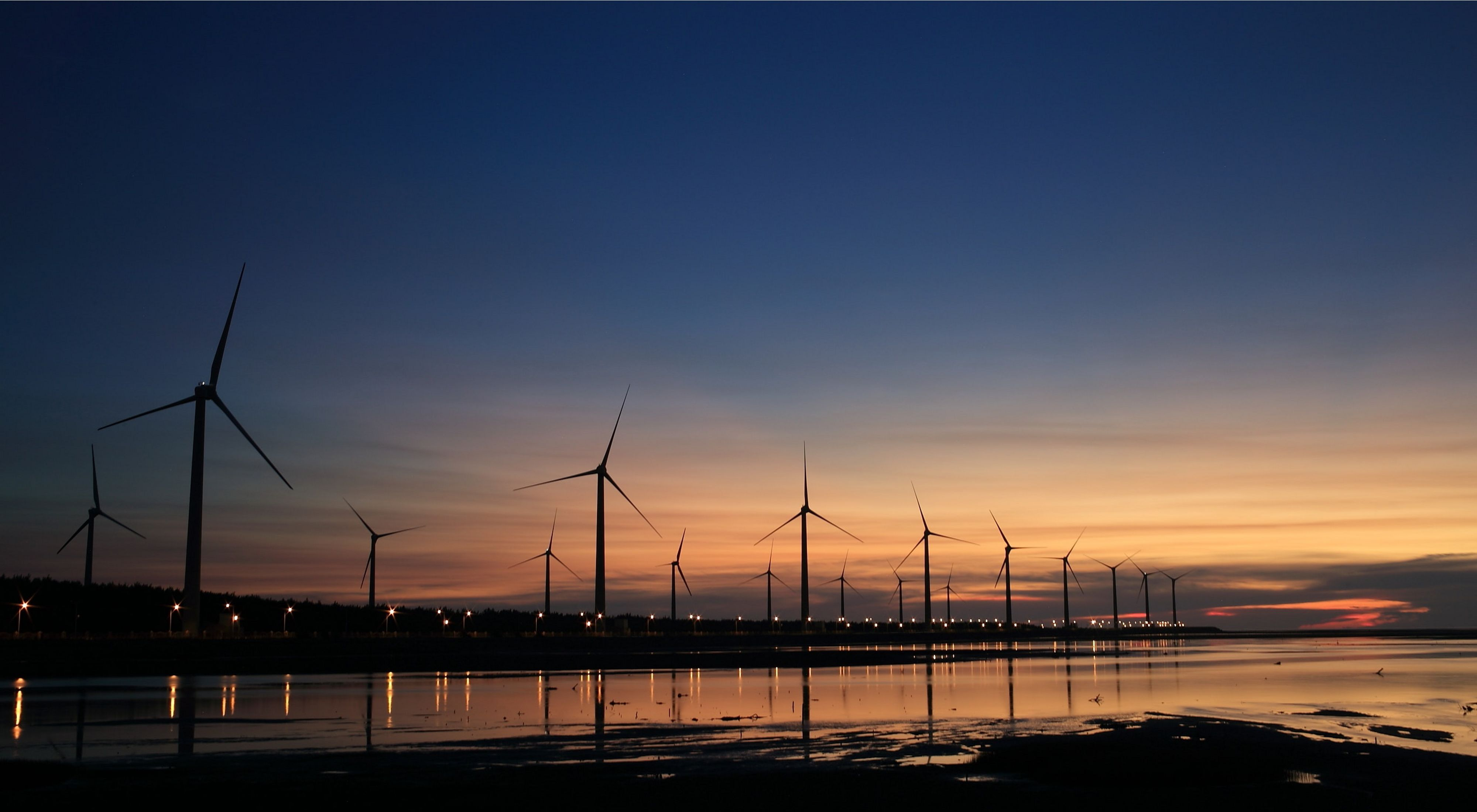 Wind turbines dot a shoreline at sunset.
