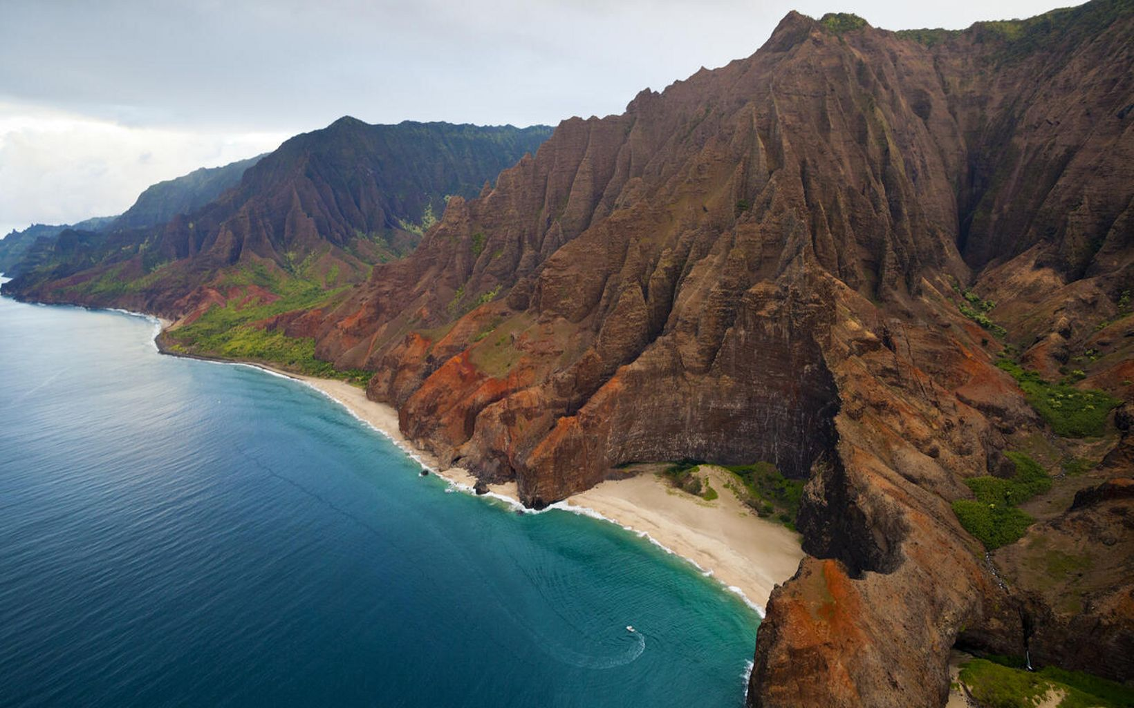 Aerial view of a tour boat near the high cliffs of the Na Pali Coast in Hawaii.