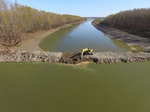 An aerial view of a backhoe cutting a notch in a dike at Coffee Point on the Mississippi River.
