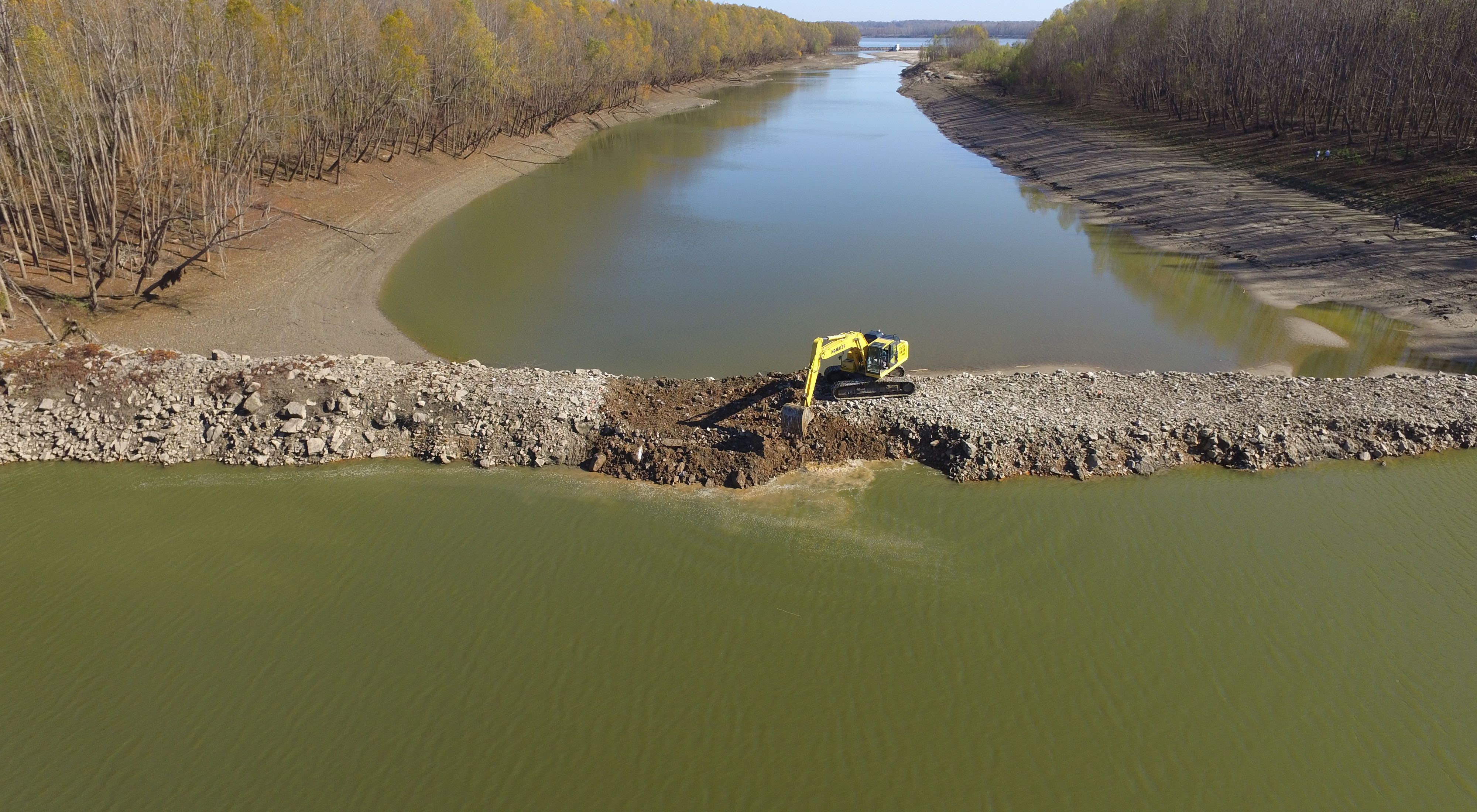 An aerial view of a backhoe cutting a notch into a dike at Coffee Point on the Mississippi River
