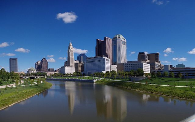 Standing on a concrete bridge and looking downstream at a calm river with the city of columbus skyline as a backdrop.