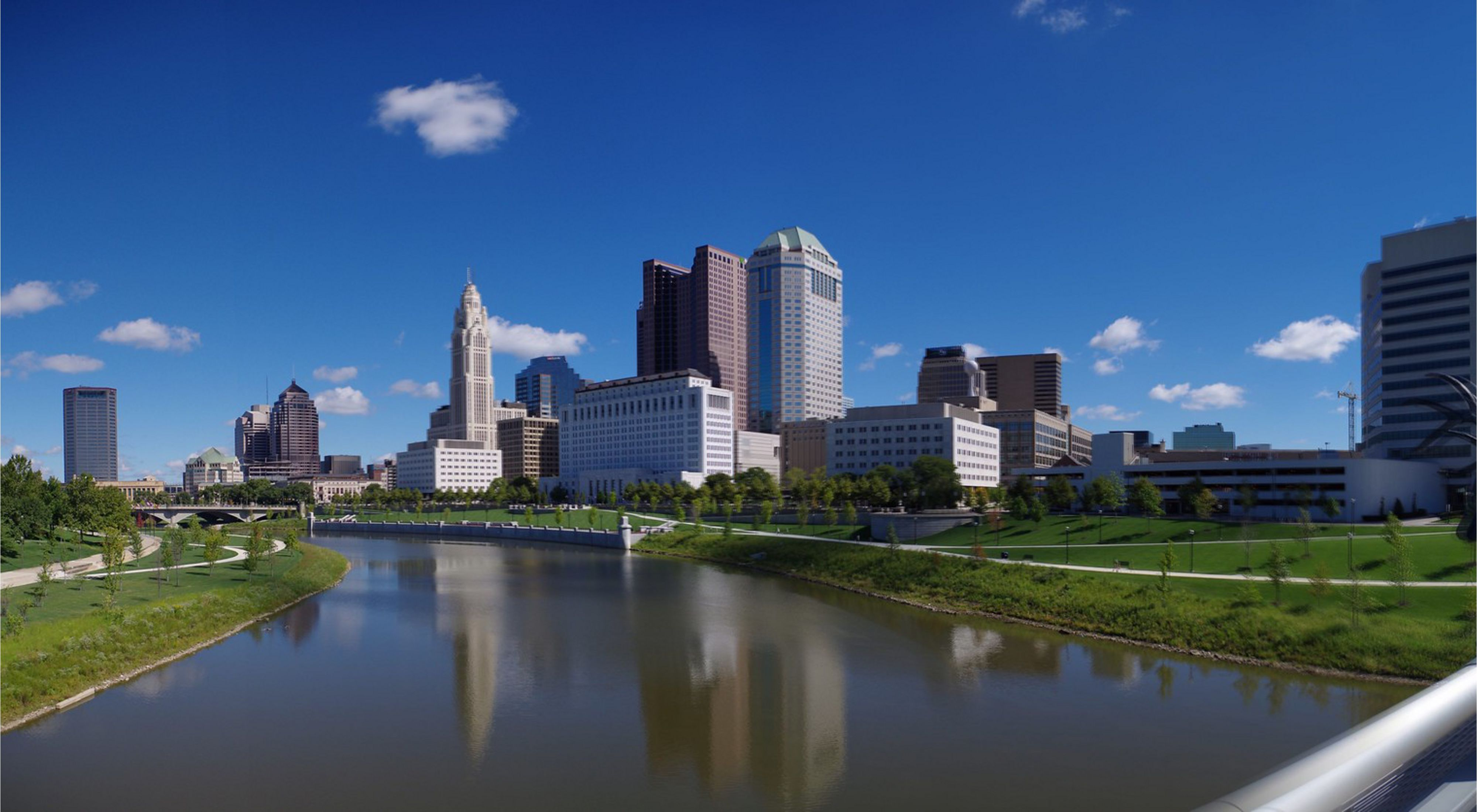 A bright blue sky is the backdrop for the city skyline, while a river flows diagonally across the foreground.