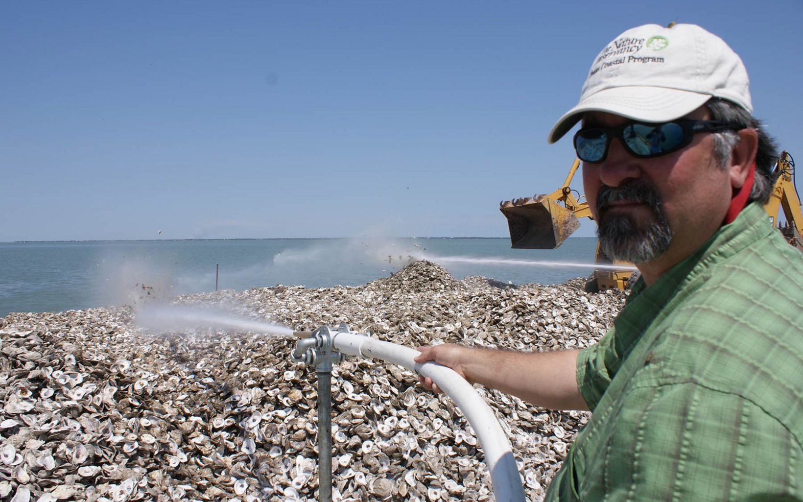 (LIMITED INTERNAL RIGHTS) April 2008 - Corpus Christi, Texas. Mark Dumesnil (Nature Conservancy upper Gulf Coast program manager) blows oyster shells into Copano Bay with a fire hose to restore oyster reefs for oysters and fish. Photo credit: © Mark Gagliano