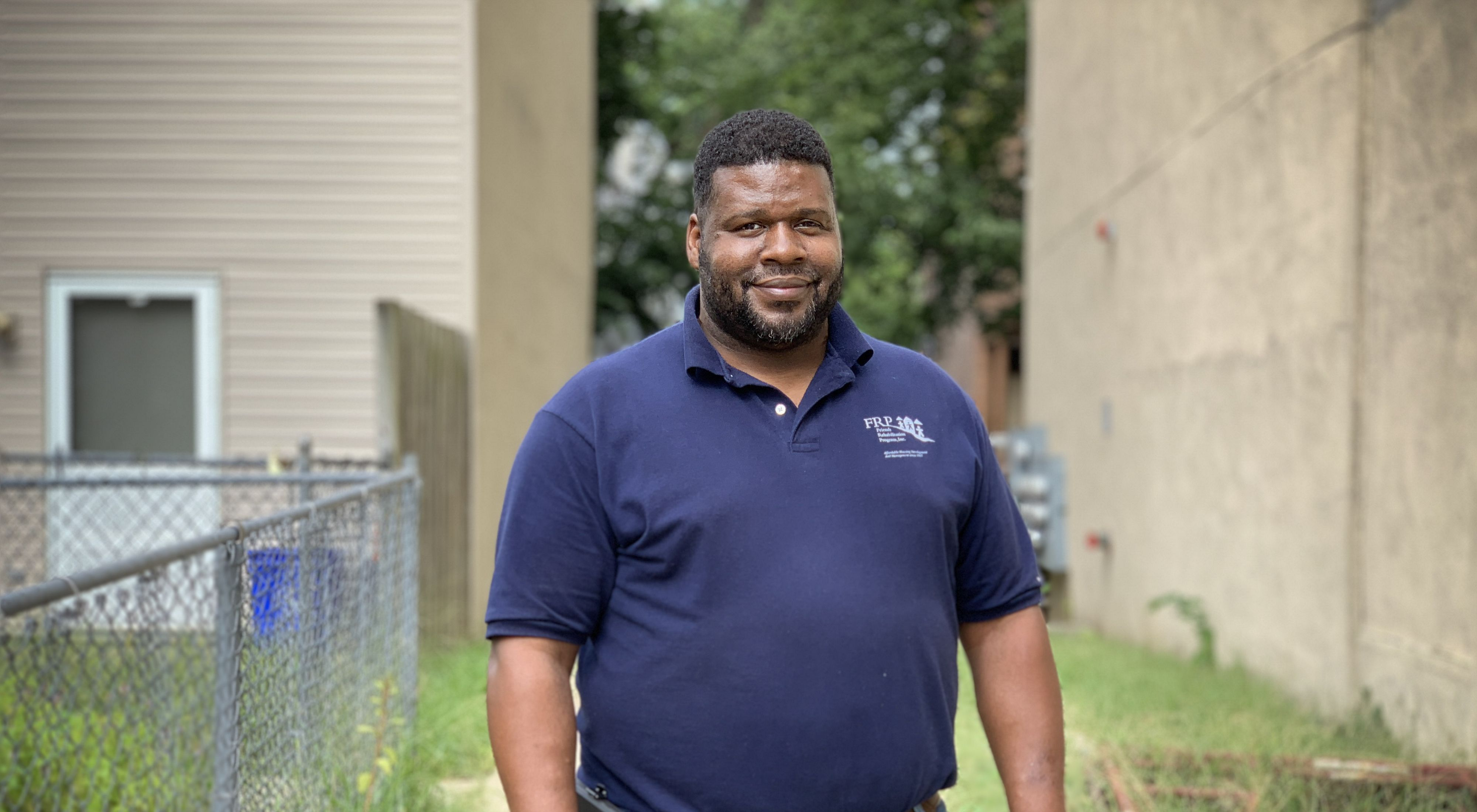A smiling man in a blue shirt stands in a residential neighborhood between two houses.