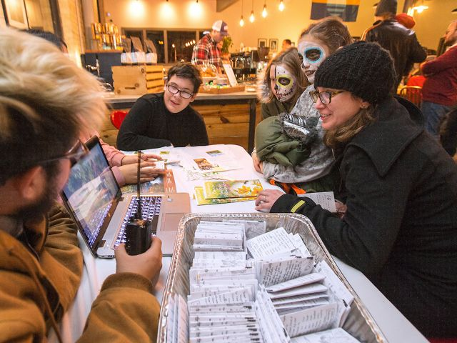 Three young people sit at a table at an event with an open laptop and seed packets in front of them talking to two young girls with their faces painted to look like skeletons.
