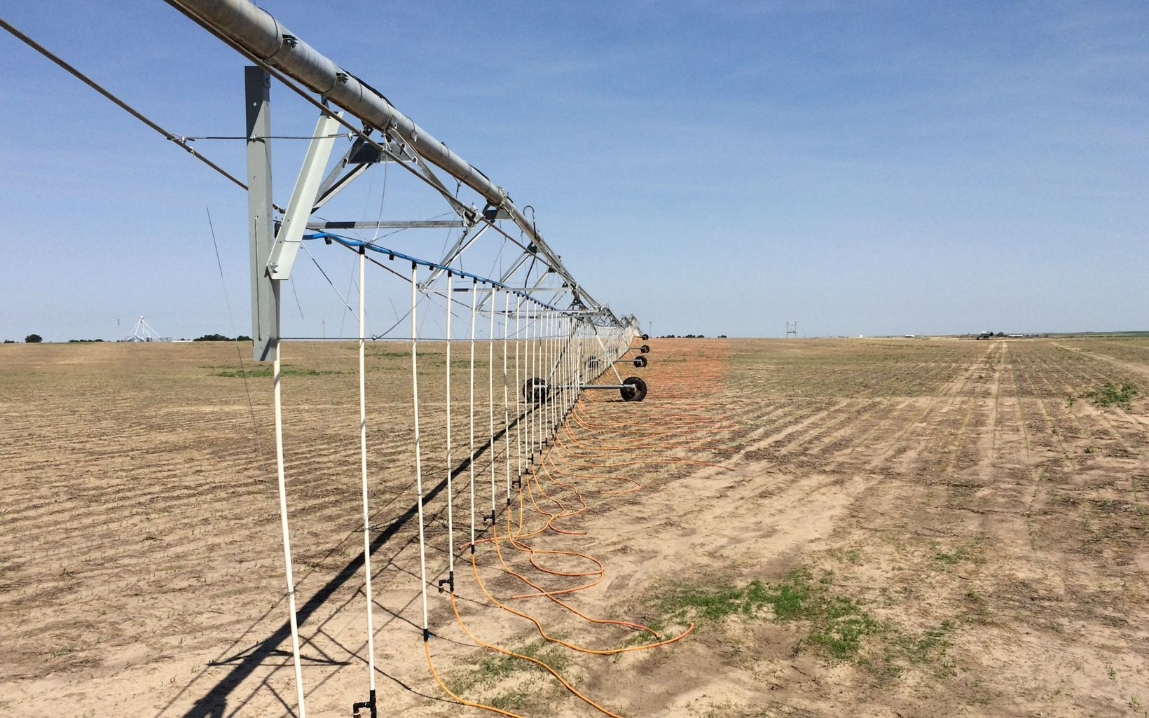 An irrigation arm on wheels extends away from the camera with small pipes and hoses running down to the ground at regular intervals to water a field.