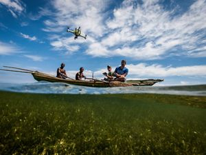 four men sit on a boat and pilot a drone against a blue sky