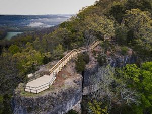 A bird's eye view of a wooden platform and trail that overlooks a breathtaking view of forest covered hills.