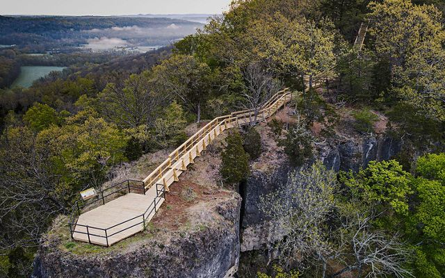 A bird's eye view looking down on a wooden platform and trail that overlooks a breathtaking forest.
