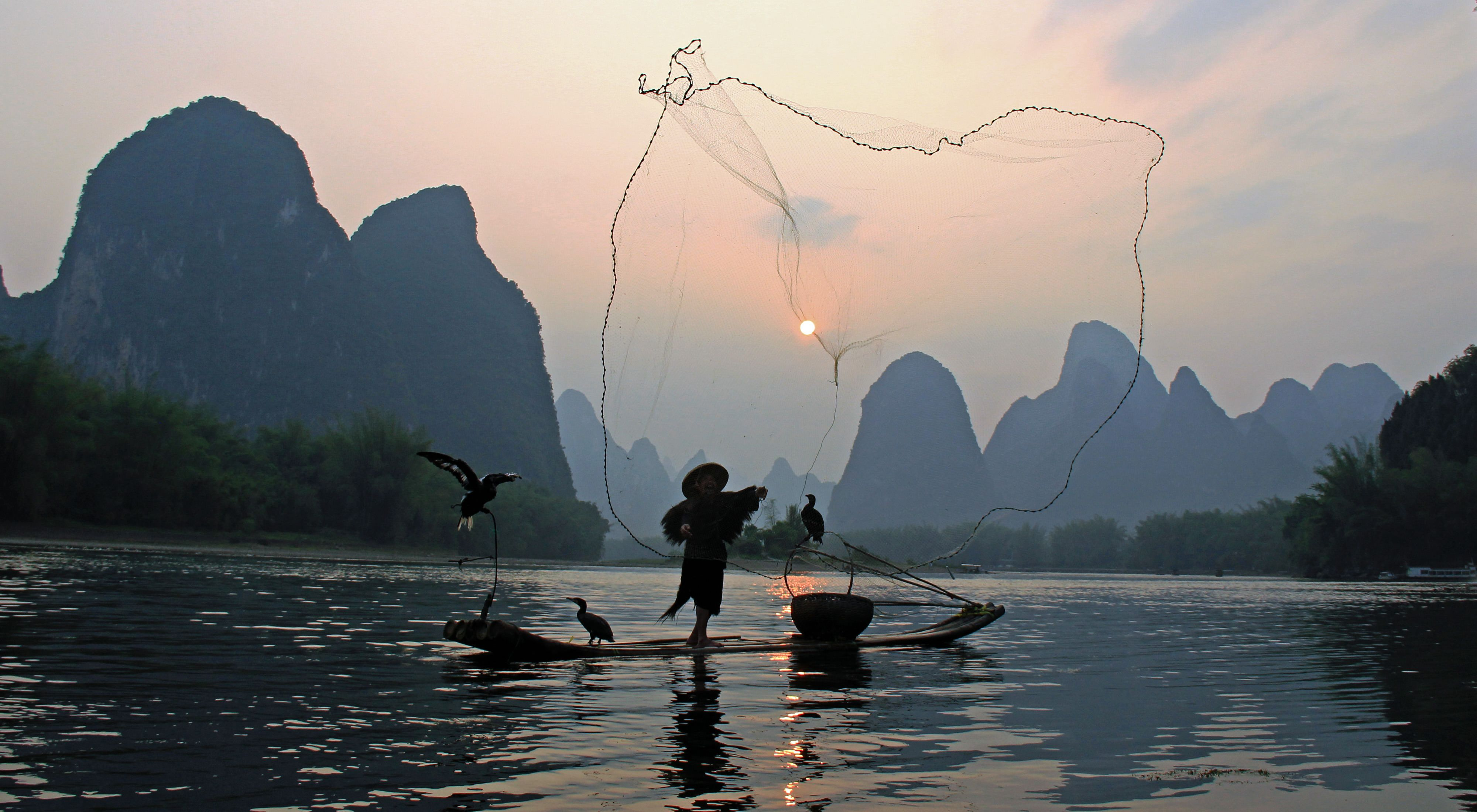 on the Li River during a misty, cloudy evening in Guangxi, China.