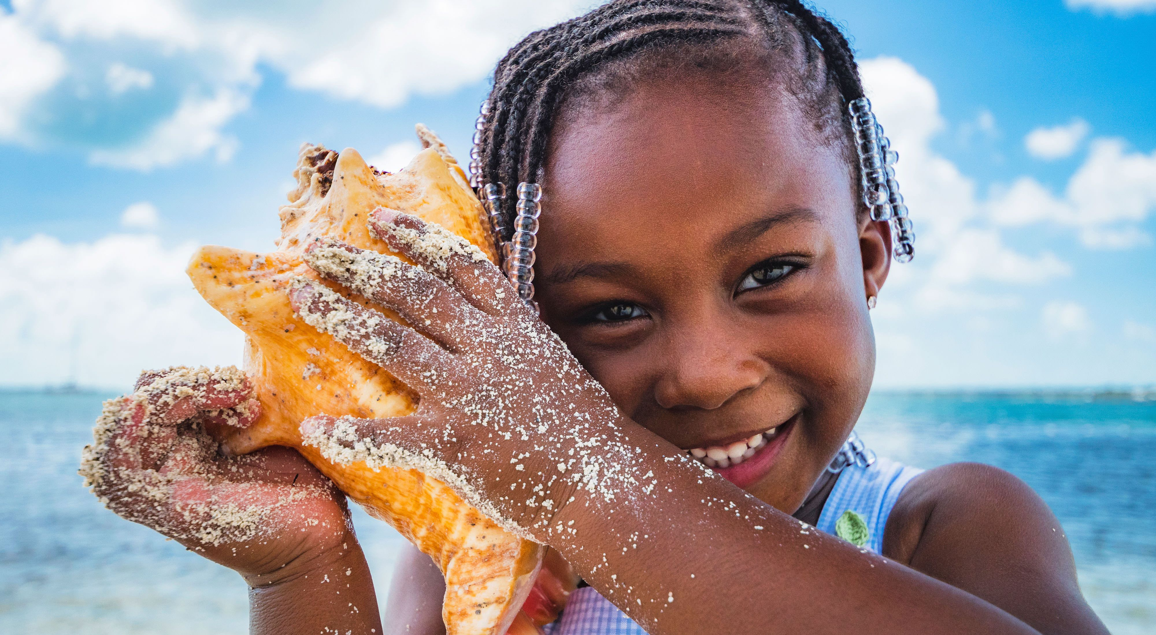 Girl smiles at camera holding a conch shell with hands covered in sand and blue ocean in background.