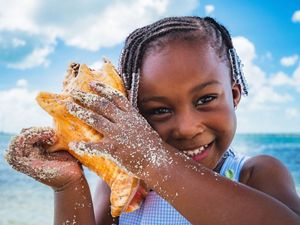 Girl plays with conch shell on beach in The Bahamas.