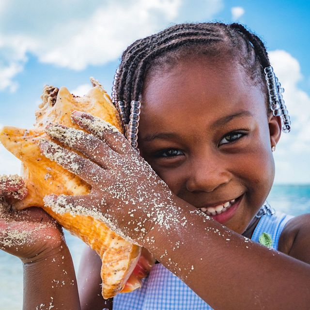 A young Bahamian girl plays with a conch shell on a New Providence Island beach in The Bahamas.