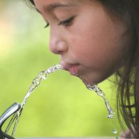 Girl drinking water from a fountain.