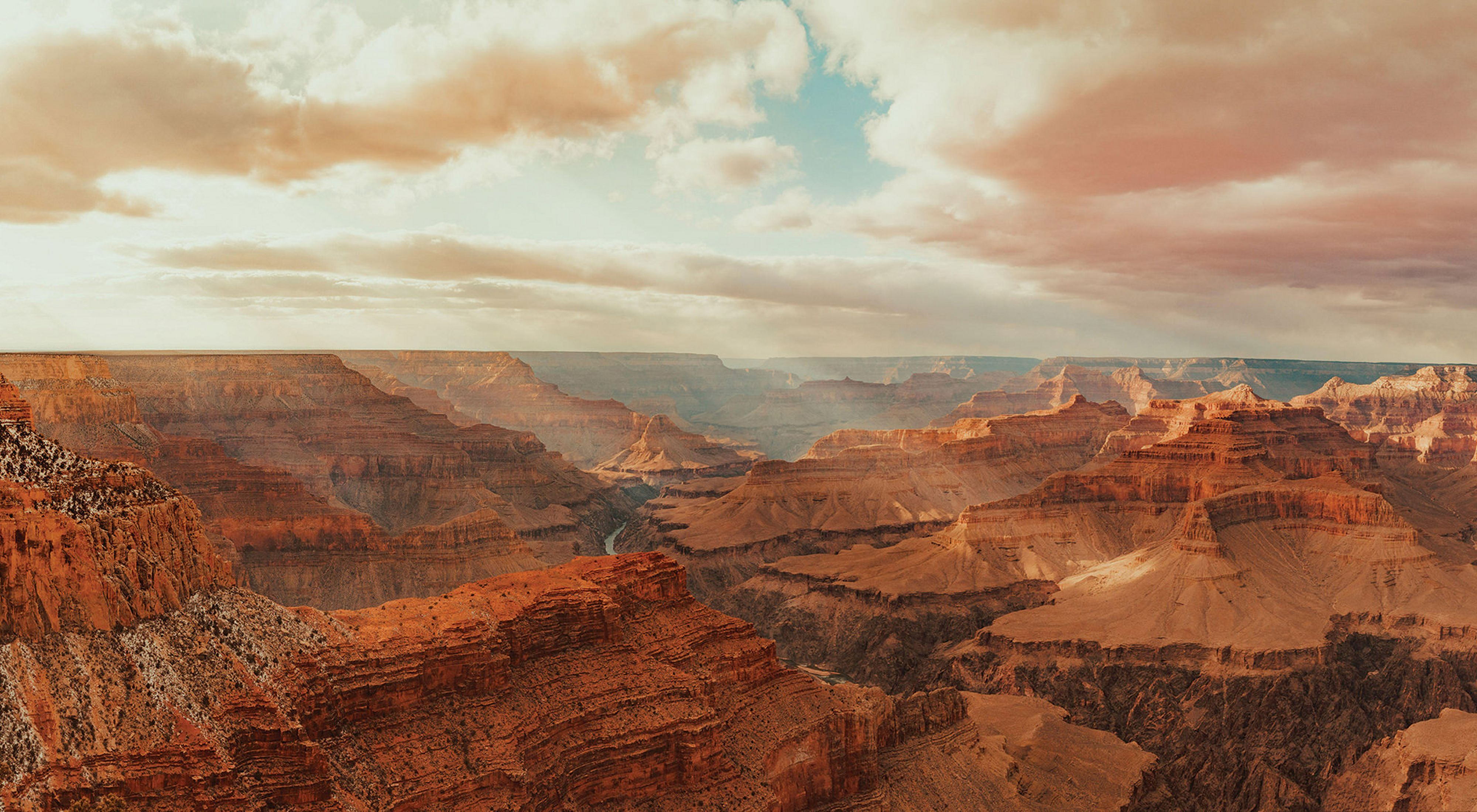 Bright golden sun rays fall over the red-colored Grand Canyon under a mostly cloudy sky.