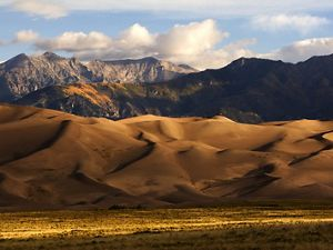 Sunrise at Great Sand Dunes National Park and Preserve with the Crestone Peaks of the Sangre de Cristo Mountains in the background.