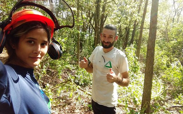 A woman wearing an orange helmet, standing in a forest, is looking at the camera, a man is standing beside her showing a thumbs up.