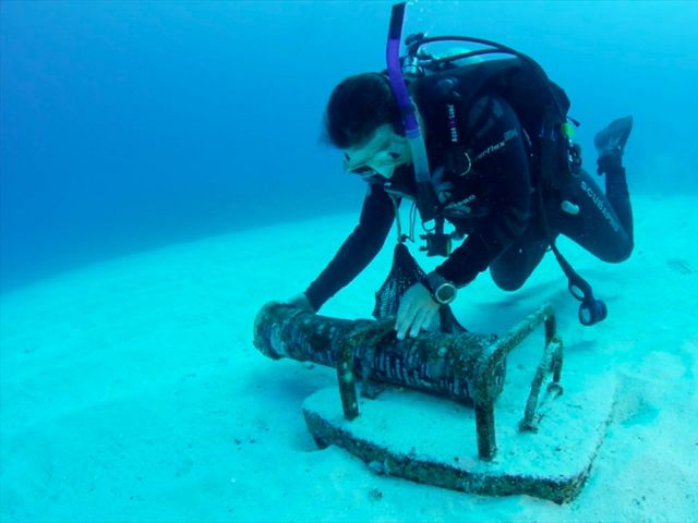 Underwater photo of a diver deploying a large recording device on the sandy sea floor.