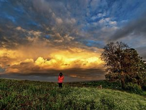 A woman looks out at thunderclouds in the distance.