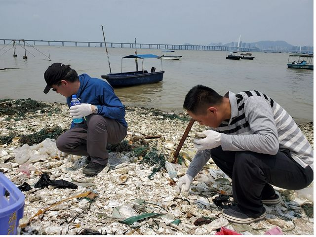 Two people are crouched down to sort through a pile of discarded oyster shells.
