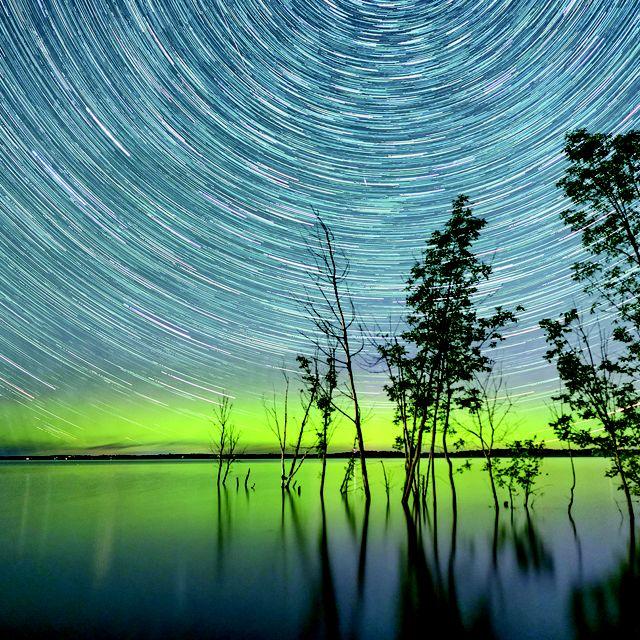 Imagen que muestra el aparente movimiento de las estrellas en el firmamento nocturno según el transcurso del tiempo.