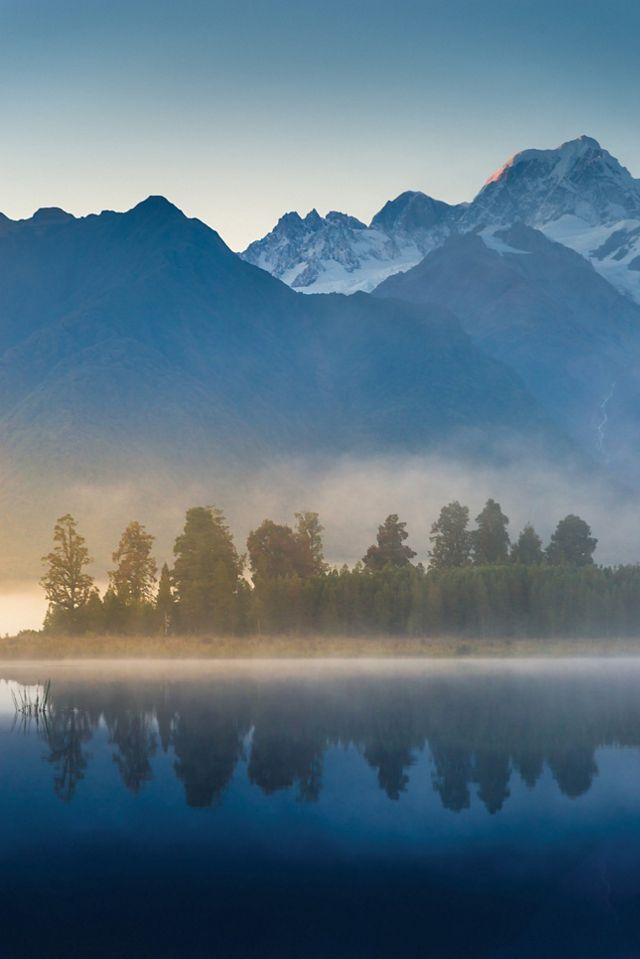 reflected in Lake Matheson at sunset in New Zealand.