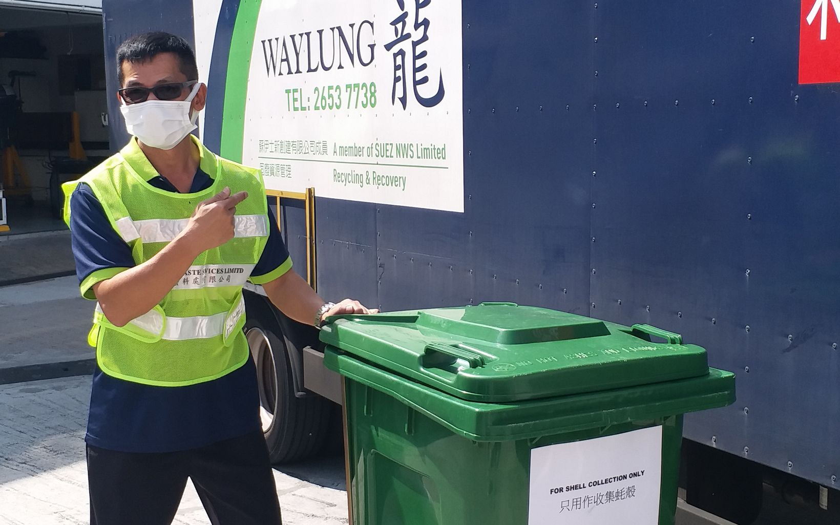 A trash collector stands next to a blue trash container in front of a large truck.