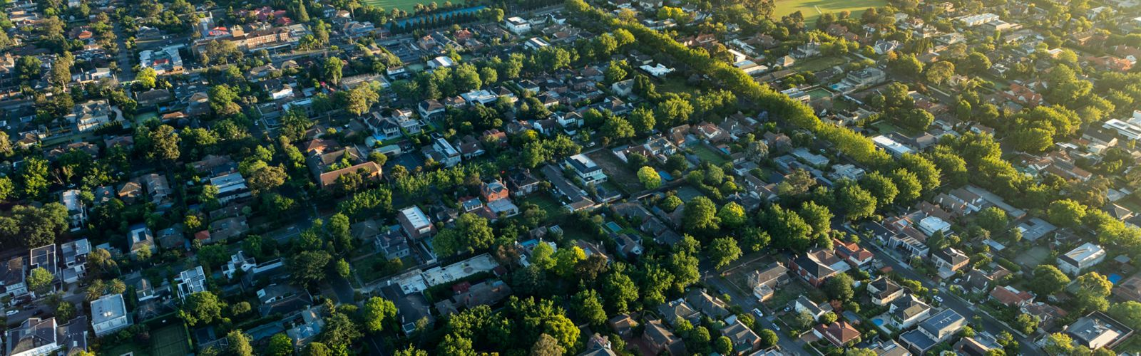 aerial view of suburban neighborhood with houses and buildings and lots of trees throughout